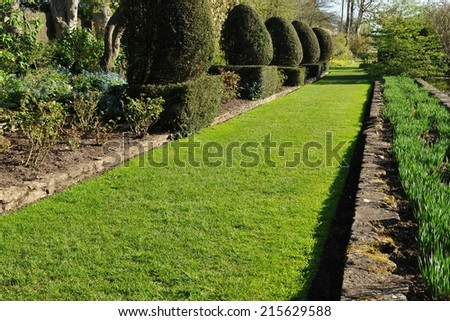 View of a Grass Pathway in a Peaceful Garden - stock photo
