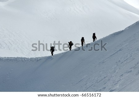 View of a group hiking on slope of high Alps mountains. - stock photo