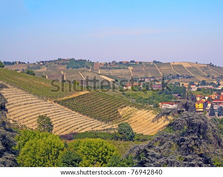 View of a hill with vineyard under blue sky - stock photo