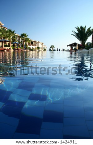 view of a hotel swimming pool from the surface of the water - stock photo