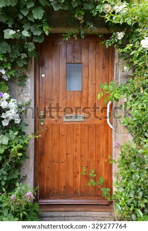 View of a House Front Door of Surround with Plants and Flowers - stock photo
