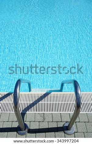 View of a ladder for entering in a crystal clear blue  swimming pool water