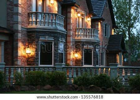 view of a large luxurious home in the evening after a light rain - stock photo