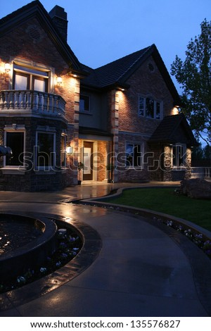 view of a large luxurious home in the evening after a light rain with the house lit up