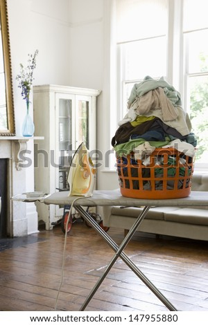 View of a laundry basket with iron on ironing board at home - stock photo