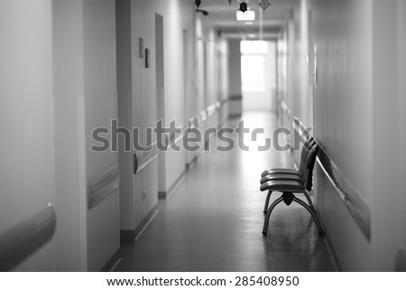 View of a long hospital hallway with free seats - stock photo