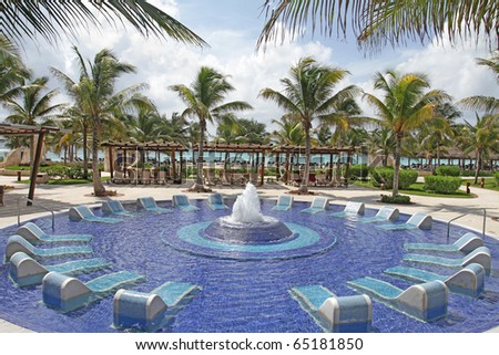 View of a luxury resort, palm trees and tropical pool