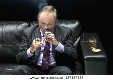 View of a mafia sitting on black couch and lighting a cigar