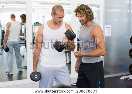 View of a male trainer assisting young man with dumbbell in the gym