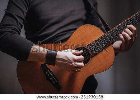 View of a man's hands playing on acoustic parlour guitar - stock photo