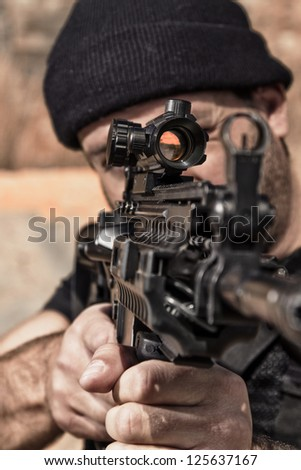 View of a man with a machine gun on a stone quarry.