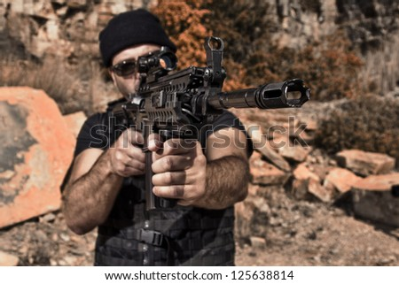 View of a man with a machine gun on a stone quarry. - stock photo