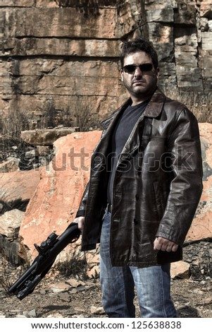 View of a man with a shotgun in jeans and jacket on a stone quarry. - stock photo