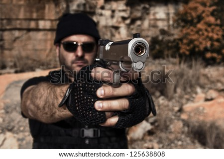 View of a man with dark shades pointing a gun to the camera.