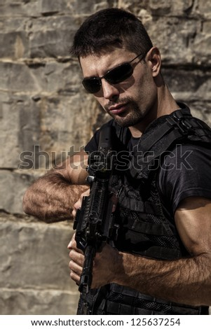 View of a menacing man with a machine gun in a black shirt and dark shades on a stone quarry. - stock photo