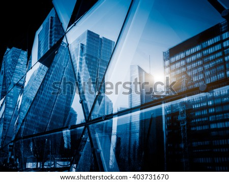 View of a modern glass skyscraper reflecting the buildings around,blue toned image. - stock photo