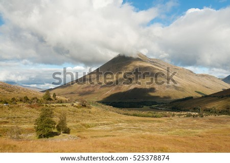 View of a mountain in Glen Coe, Scottish Highlands, United Kingdom, while clouds gather on top of the hill, casting a shade on the ground and trees can be seen on the foreground.