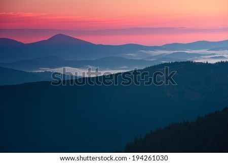 View of a mountain valley in a beautiful early morning with fog between hills