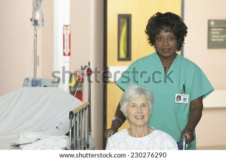 View of a nurse pushing a patient in a wheelchair into a hospital room - stock photo