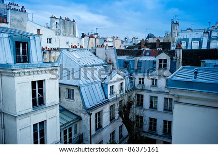 View of a Paris neighborhood skyline, featuring mostly rooftops from the top floor of an apartment building in Paris, France. - stock photo