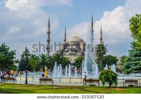 View of a park full of people admiring majestic fountain and blue mosque behind it in istanbul. - stock photo