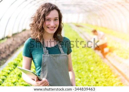 View of a Portrait of an attractive farmer in a greenhouse using tablet