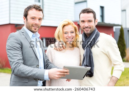 View of a Real estate agent and a young couple in front of their next home