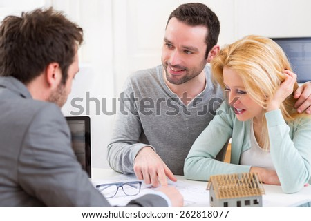 View of a Real estate agent present project on blueprint to a young couple