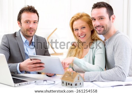 View of a Real estate agent present project on tablet to a young couple