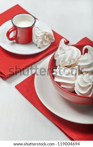 View of a red bowl with white meringues on a red textile napkin. In the distance is a red cup with milk and a broken piece of meringue on a plate. - stock photo