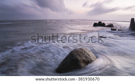 View of a rocky coast during sunset. Long exposure shot