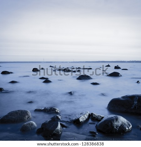 View of a rocky coast in the evening. Long exposure shot. Black and white image - stock photo