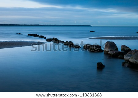 View of a rocky coast in the morning. Long exposure shot. - stock photo