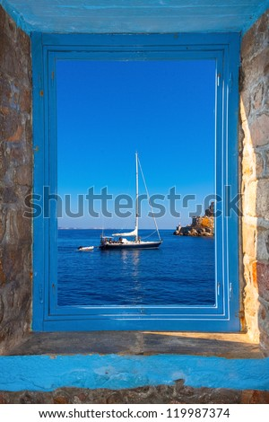 View of a sailing boat threw a window  in Santorini island Greece - stock photo