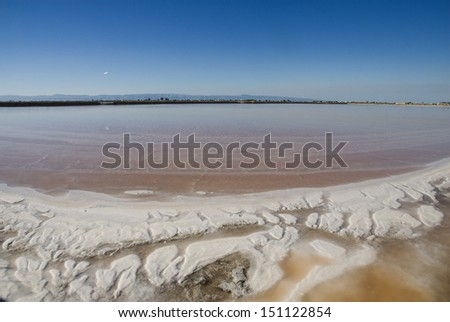 View of a salina in southern Italy. Making salt from sea water in 'Margherita di Savoia'. - stock photo