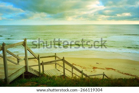 View of a sandy beach from the sand dune and staircase in retro style - stock photo