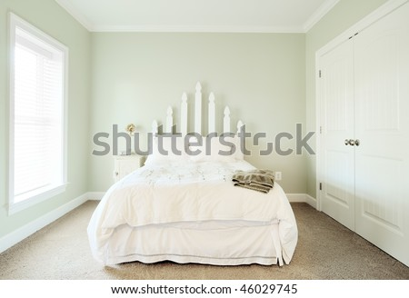 View of a simple upscale bedroom, decorated in light neutral shades. Horizontal format. - stock photo