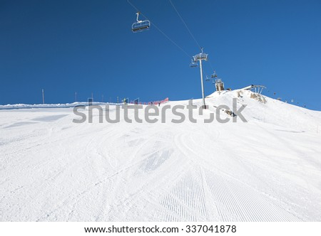 View of a snowy ski piste in alpine mountain ski resort with chairlift - stock photo