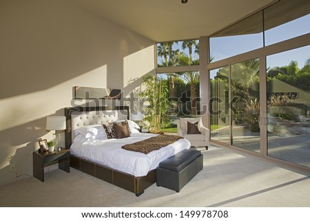 View of a spacious sunlit bedroom with porch view - stock photo