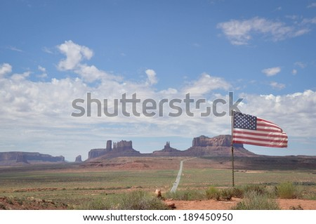 View of a street in the Monument Valley with the American Flag, USA - stock photo
