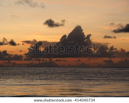 View of a sunrise, on a cloudy day, over the atlantic ocean - stock photo