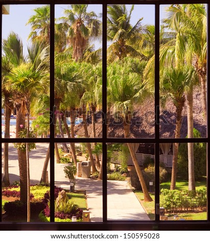 view of a tropical garden through a panoramic window - stock photo