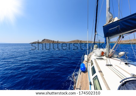View of a tropical island on the horizon in a calm blue sea from a yacht in mid-ocean looking along the deck past the cabin into a bright summer sun