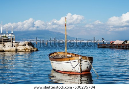 "View of a typical old wooden boat in the harbor of ""Sorrento"" in Italy"