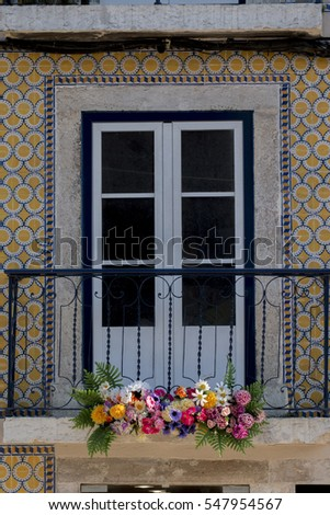 View of a typical portuguese window with flowers and azulejo tiles.