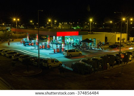 View of a urban gas station working in the evening.