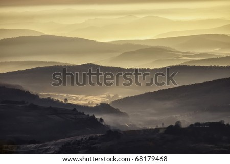 view of a valley in a beautiful early morning with fog between hills - stock photo