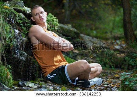 View of a very fit male model with muscles in forest