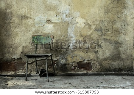 view of a wall of an old abandoned factory building,old wooden chair on moldy wall , dust  on the chair