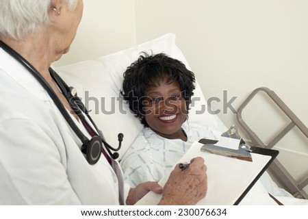 View of a woman smiling as her doctor writes on a clipboard - stock photo